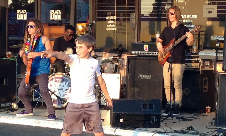 The Crazy Carls jam for craft beer festival-goers while a young fan entertains the crowd.