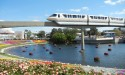 A monorail crosses over a lake lined with colorful flowers.